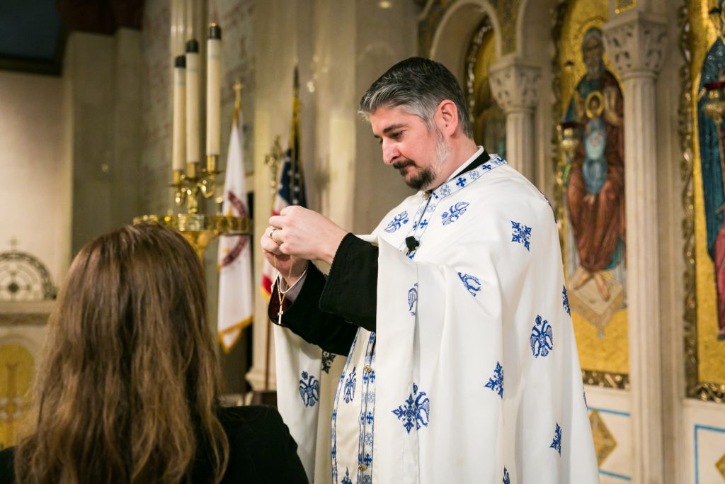 Priest holding necklace with crucifix by NYC Greek orthodox baptism photographer, Kelly Williams