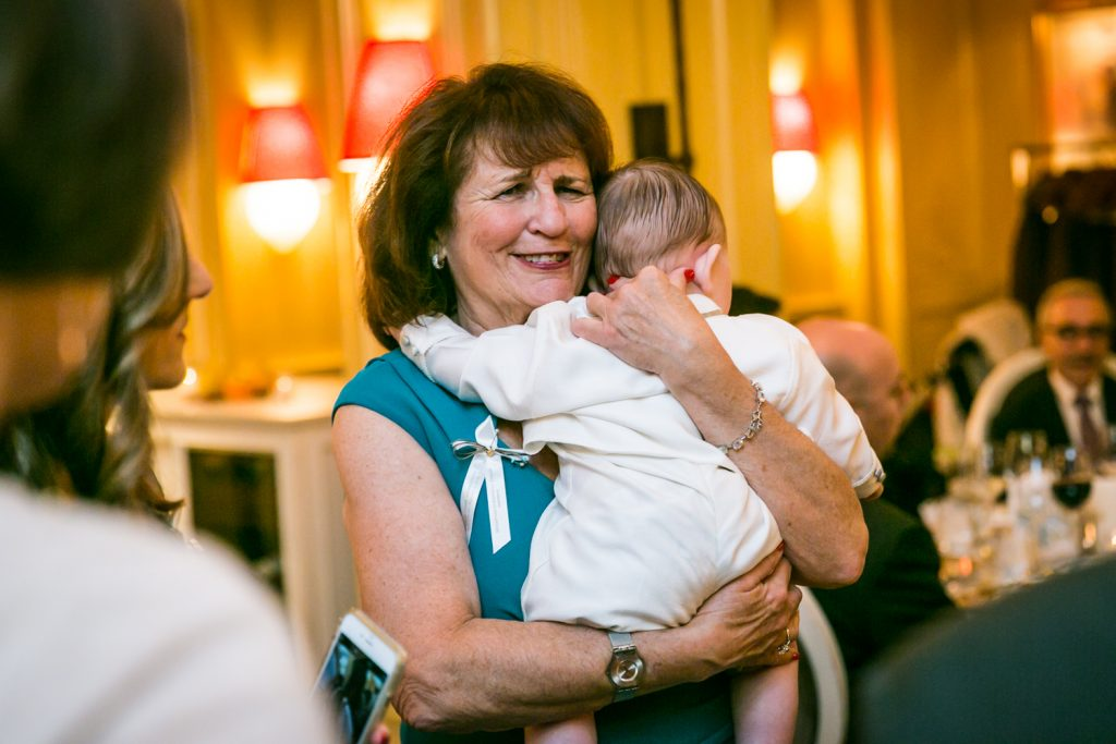 Grandmother holding baby by NYC Greek orthodox baptism photographer, Kelly Williams