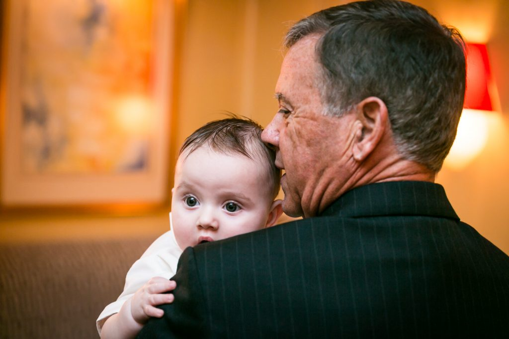 Uncle holding baby by NYC Greek orthodox baptism photographer, Kelly Williams