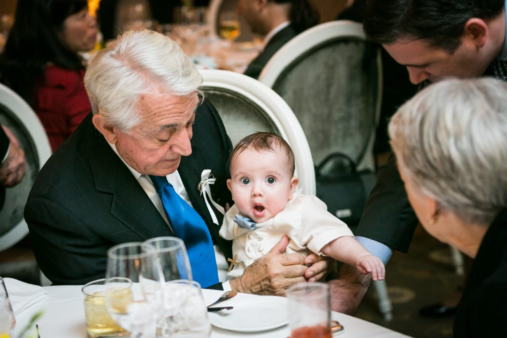 Grandfather holding surprised baby by NYC Greek orthodox baptism photographer, Kelly Williams