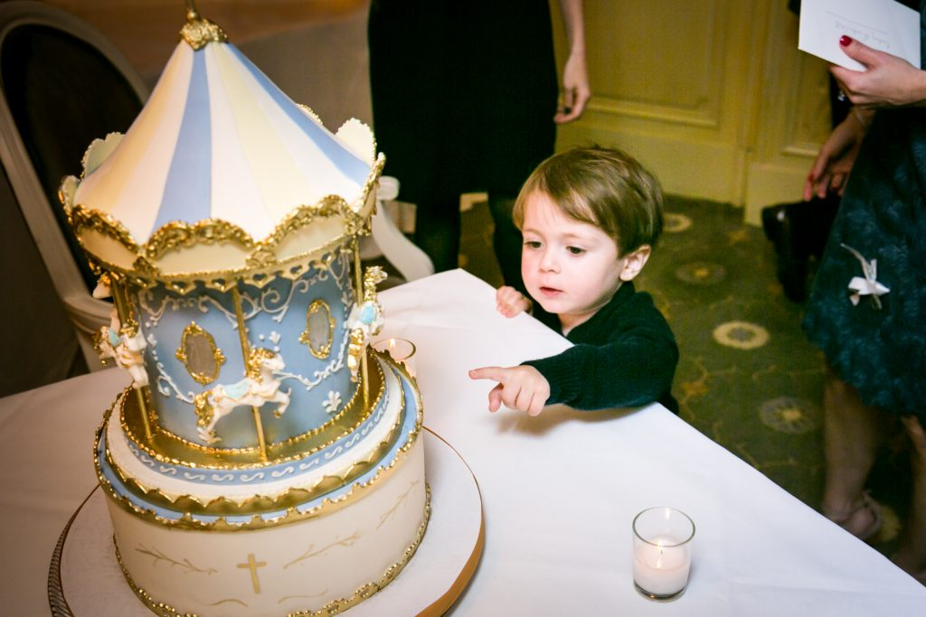 Little boy about to touch cake by NYC Greek orthodox baptism photographer, Kelly Williams