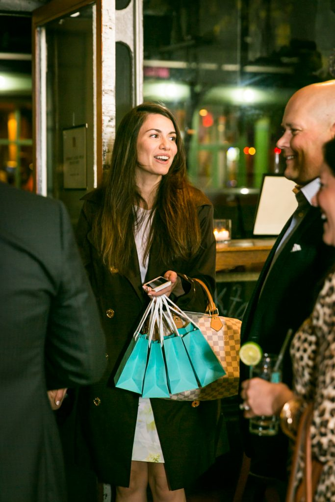 Woman holding four blue bags for an article on rehearsal dinner tips