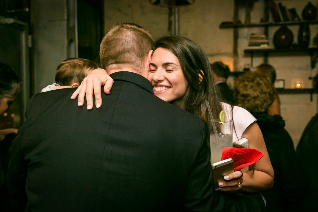 Woman hugging male guest for an article on rehearsal dinner tips