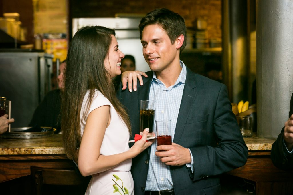 Couple talking and holding drinks during rehearsal dinner