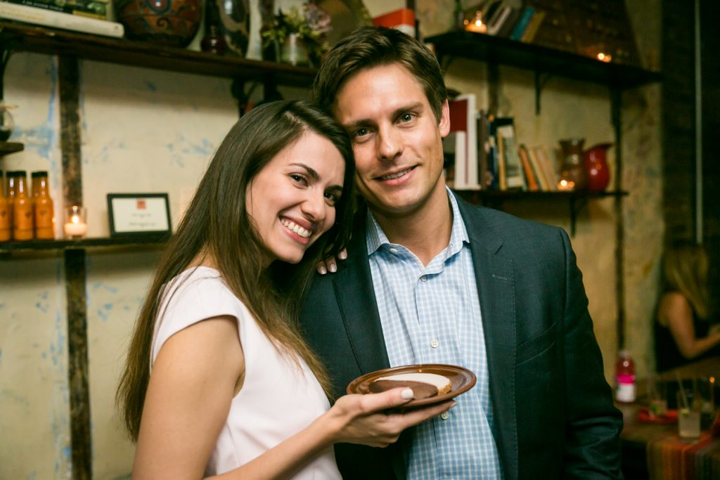 Portrait of couple with woman holding plate with cookie at rehearsal dinner