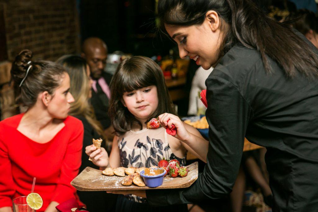 Little girl selecting appetizer at rehearsal dinner