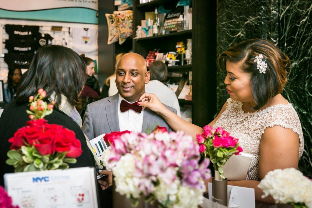 Bride adjusting groom's tie in flower shop for an article on wedding website tips
