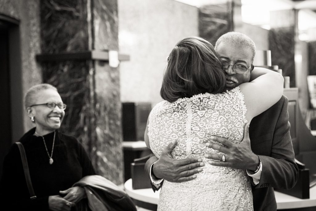 Black and white photo of bride hugging her father