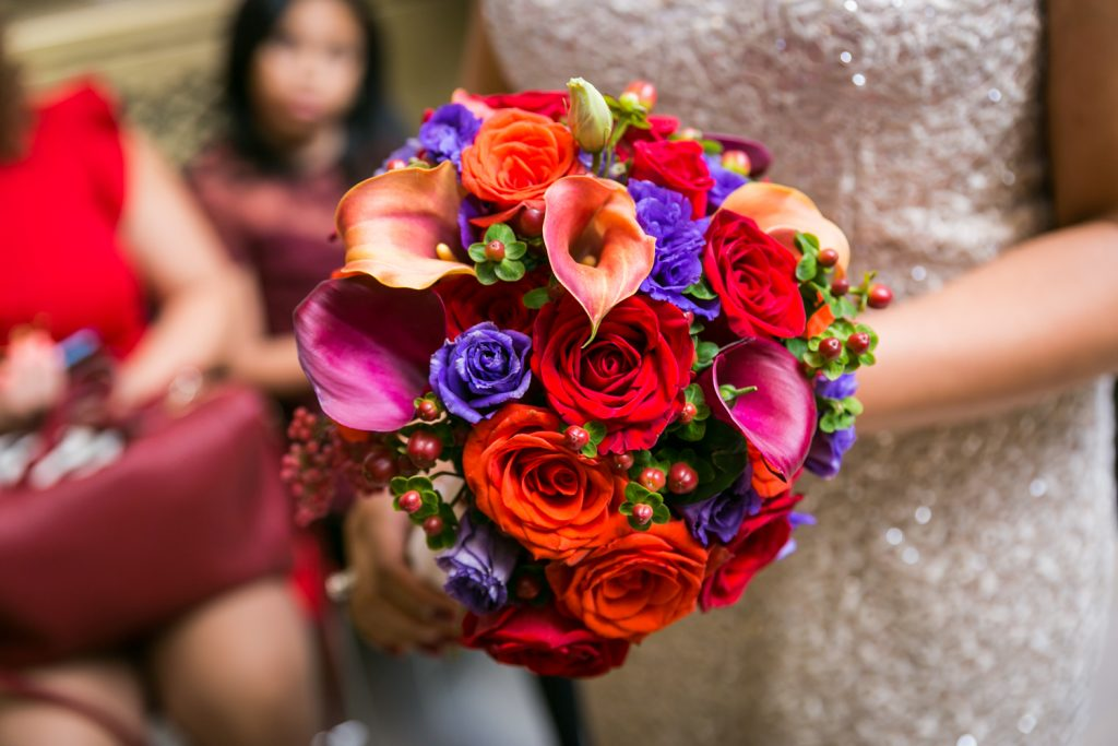 Bride's flower bouquet with red and purple flowers for an article on wedding website tips