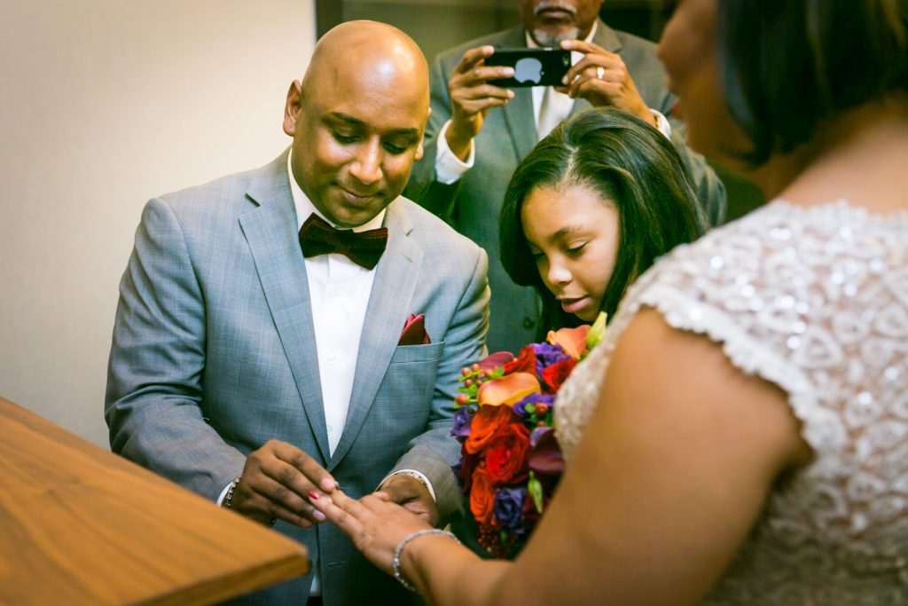Groom putting ring on bride's finger at City Hall wedding