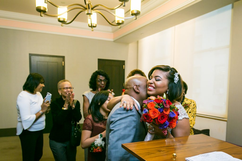 Bride hugging groom after City Hall wedding for an article on wedding website tips
