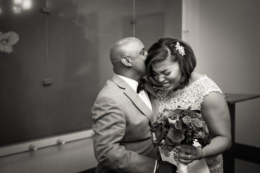 Black and white photo of groom kissing bride on her head