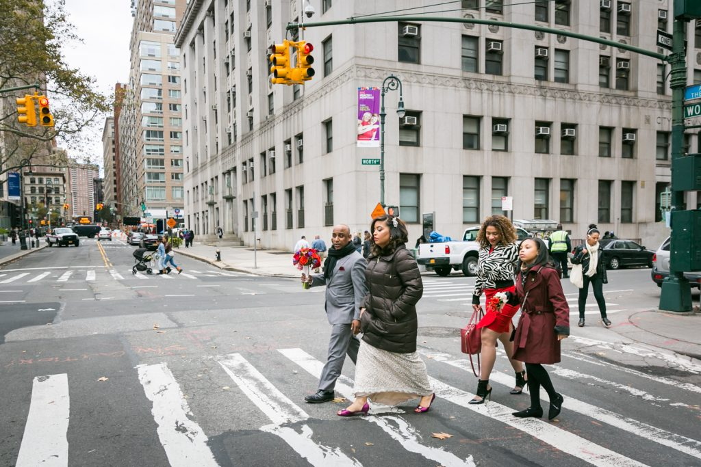 Bridal party crossing NYC street in crosswalk after City Hall wedding