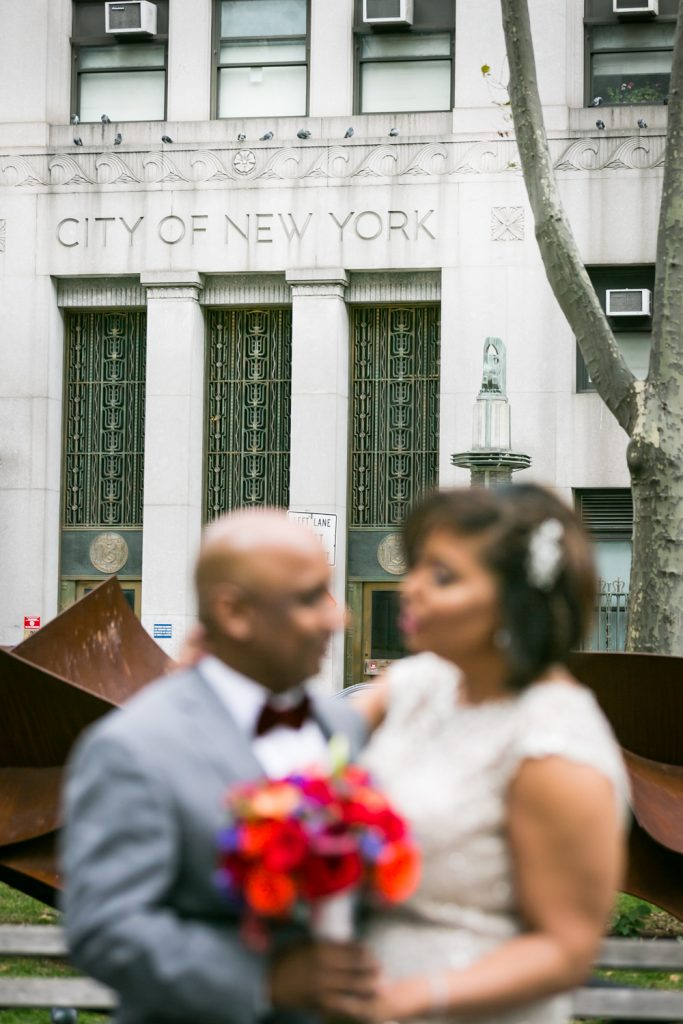 City of New York sign on building in focus in background and bride and groom out of focus in foreground
