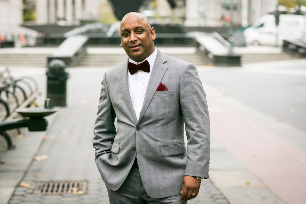 Groom wearing grey coat and red velvet bow tie for an article on wedding website tips