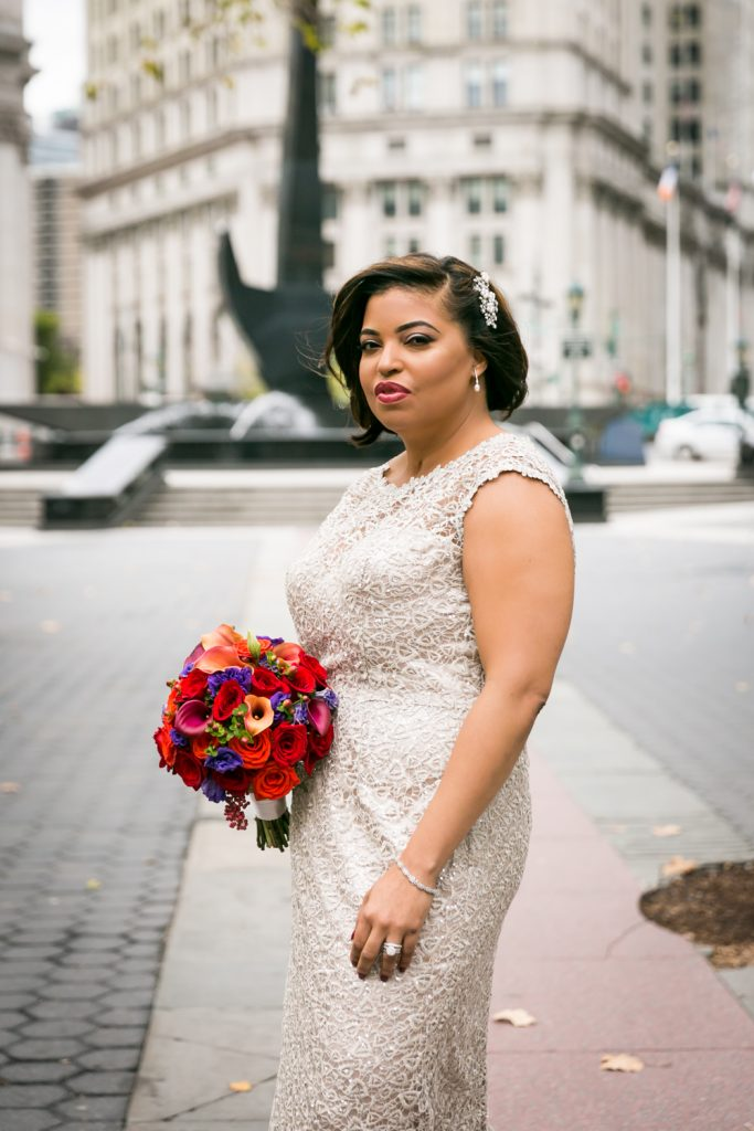 Portrait of bride wearing cream lace dress and holding flower bouquet for an article on wedding website tips