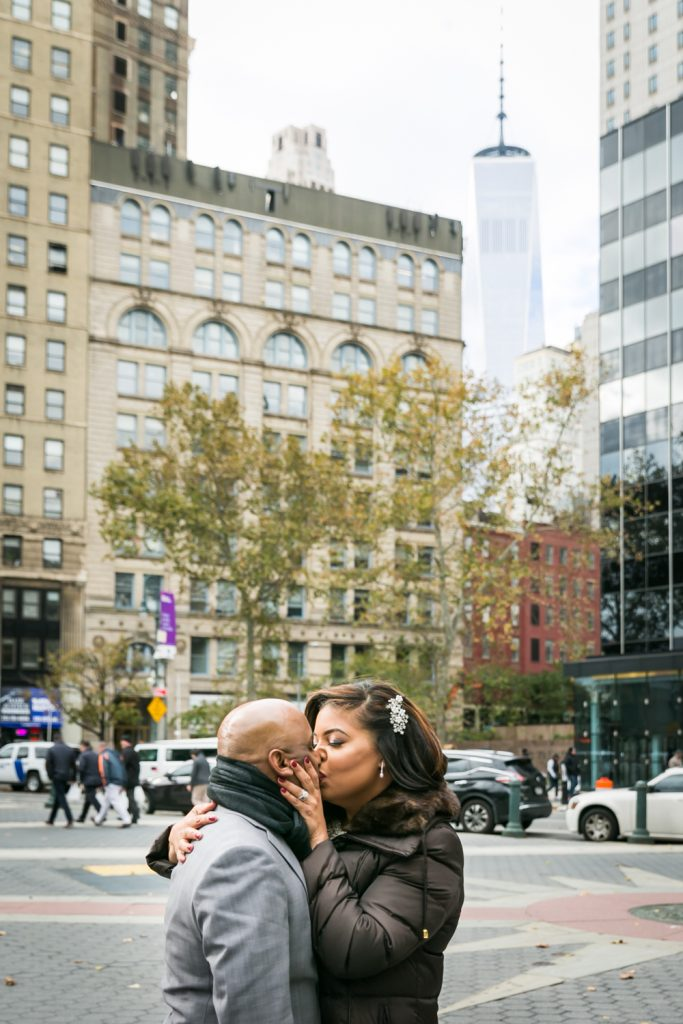 Bride and groom kissing with Freedom Tower in the background for an article on wedding website tips