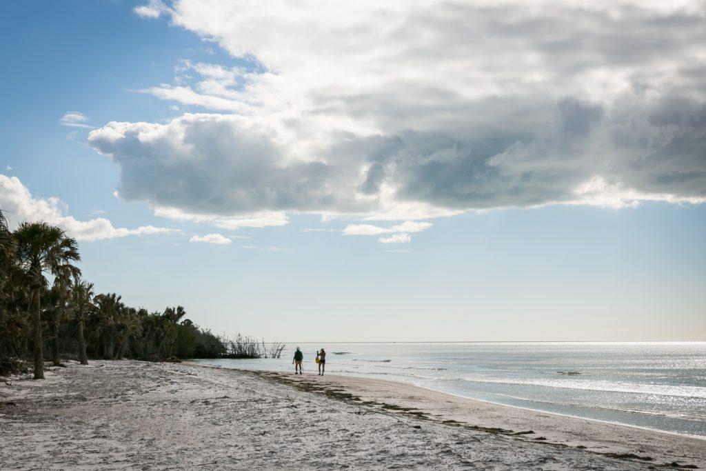 Two people walking along beach for article on Honeymoon Island photos