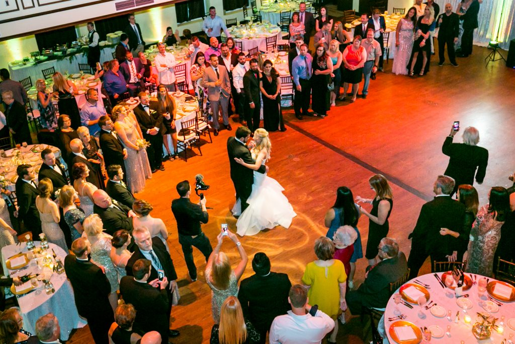 Wide shot looking down at bride and groom's first dance for an article on how DJ lighting affects your wedding photos