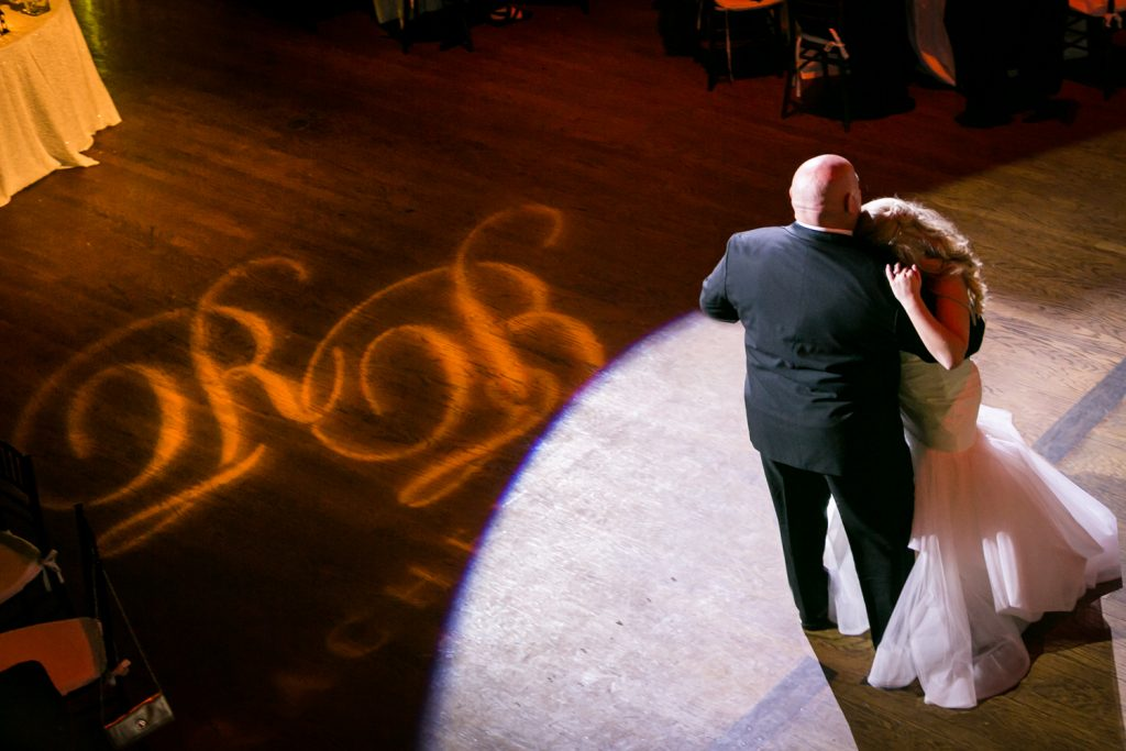 Bride dancing with father with initials in light on dance floor for an article on how DJ lighting affects your wedding photos