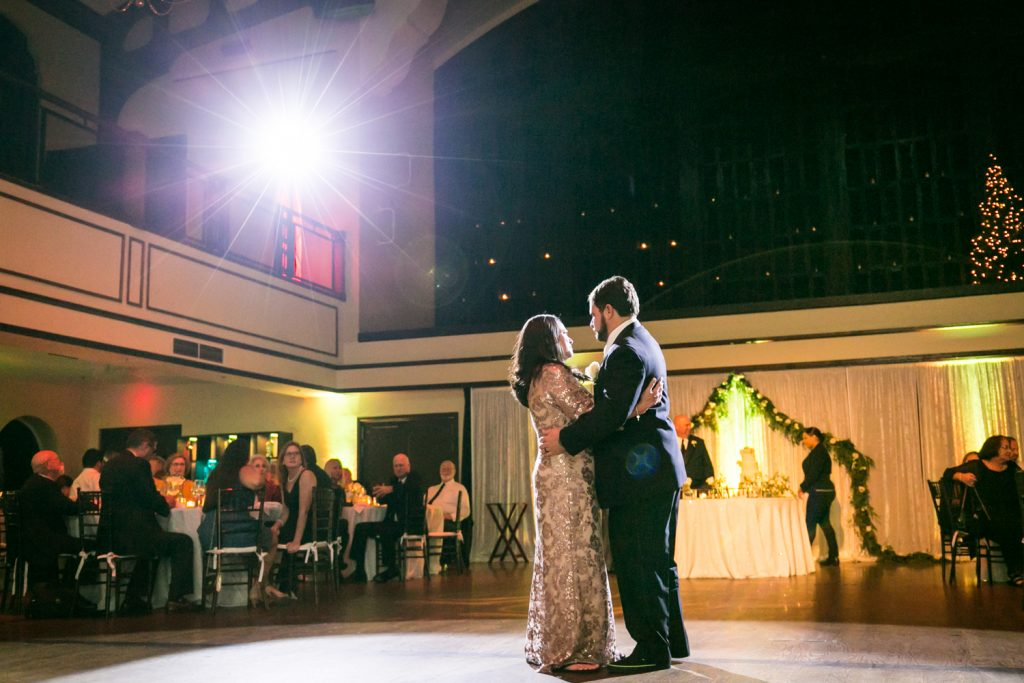Groom and mother dancing with spotlight overhead for an article on how DJ lighting affects your wedding photos