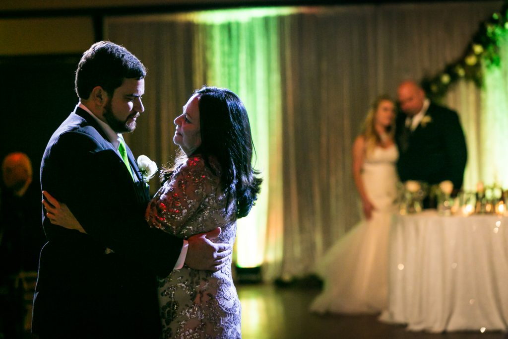 Backlit shot of groom and mother dancing for an article on how DJ lighting affects your wedding photos