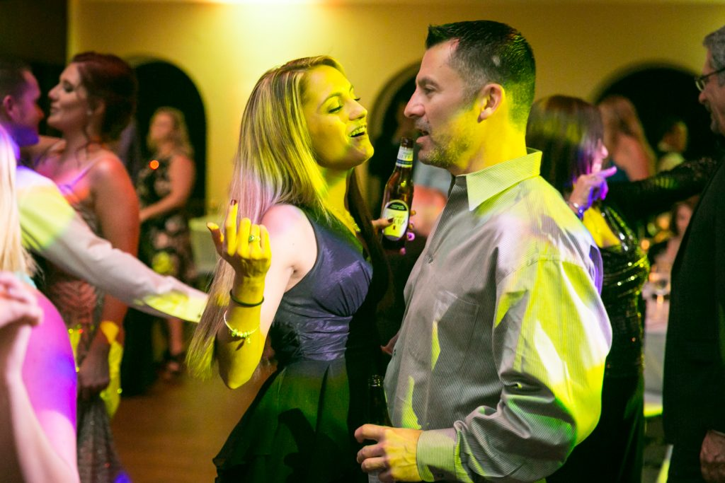 Couple bathed in yellow light dancing at a reception for an article on how DJ lighting affects your wedding photos
