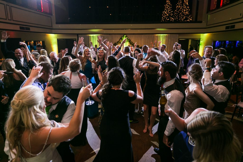 Guests on dance floor dancing with arms raised for an article on how DJ lighting affects your wedding photos
