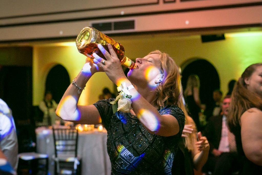 Mother of the bride drinking for bottle of Fireball for an article on how DJ lighting affects your wedding photos