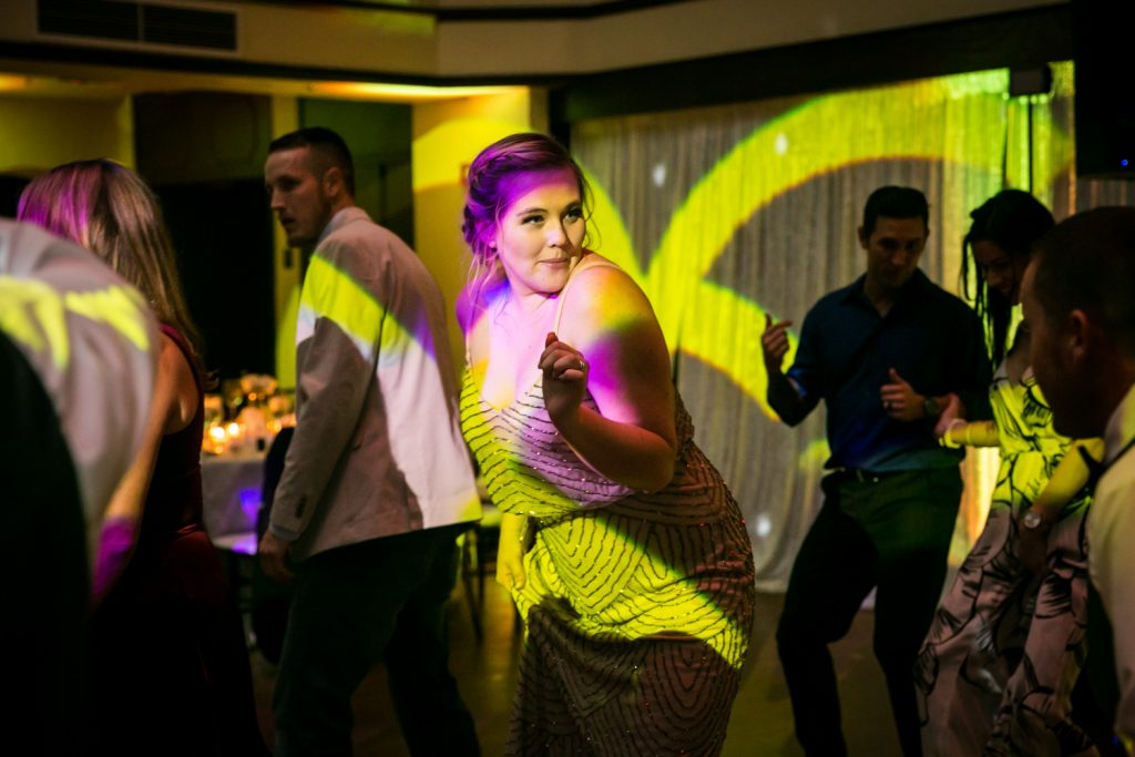 Woman bathed in pink and yellow light dancing at reception for an article on how DJ lighting affects your wedding photos