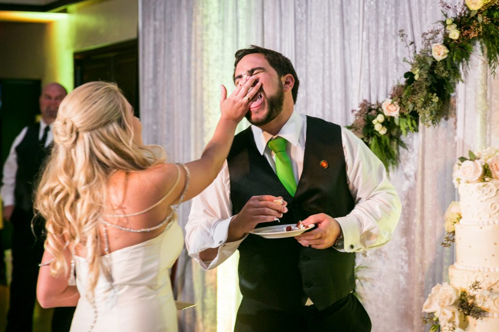 Groom shoving cake in groom's face at a West Palm Beach wedding