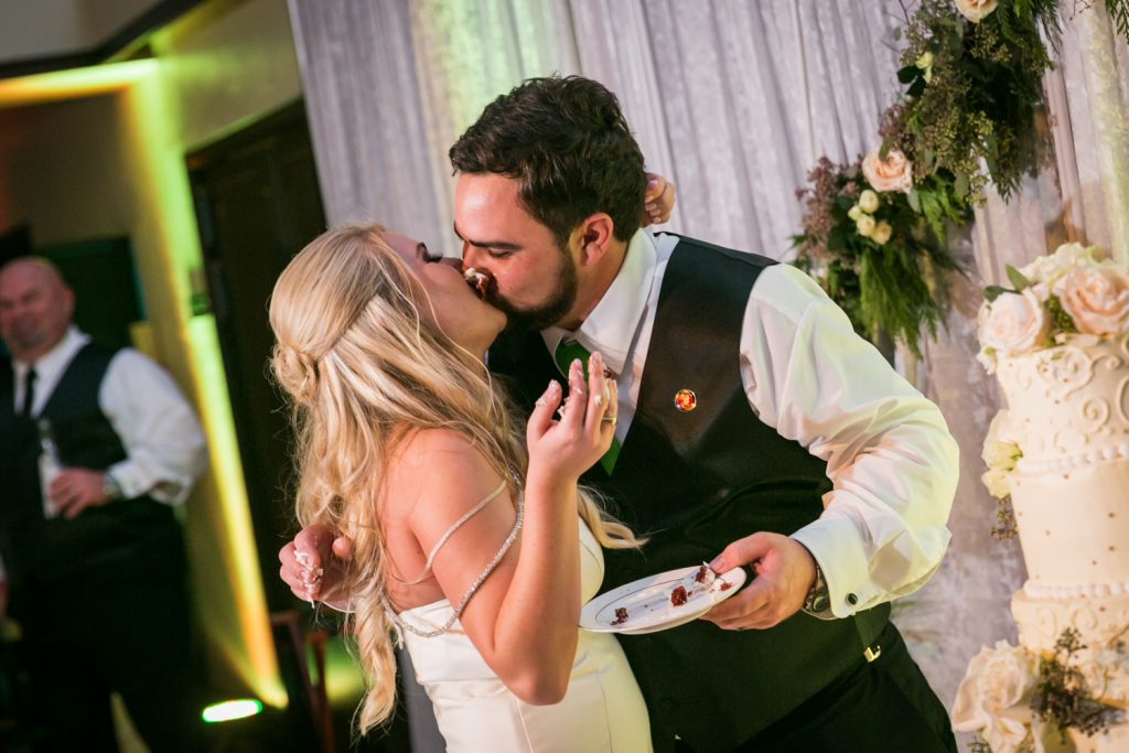 Bride and groom kissing after cutting cake at a West Palm Beach wedding
