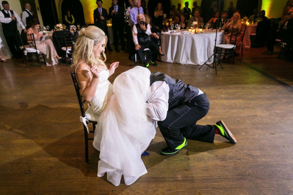 Groom under bride's dress to find garter at a West Palm Beach wedding
