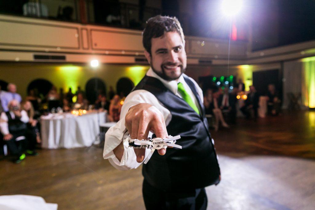 Groom showing off bride's garter belt