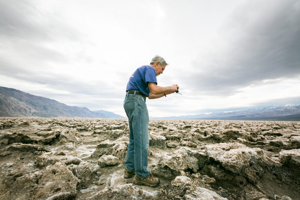 Male tourist taking photos of rock formations in the Devil's Golf Course in Death Valley National Park