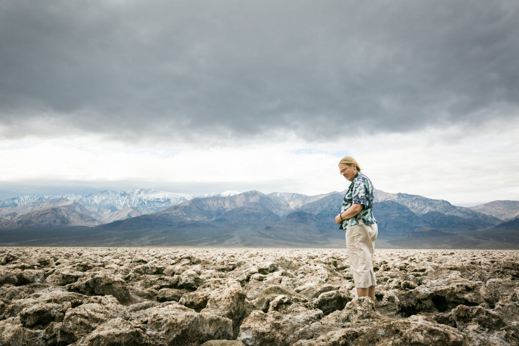 Female tourist looking at rock formations in the Devil's Golf Course in Death Valley National Park