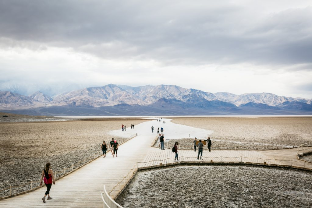 Tourists walking along boardwalk in Badwater in Death Valley National Park