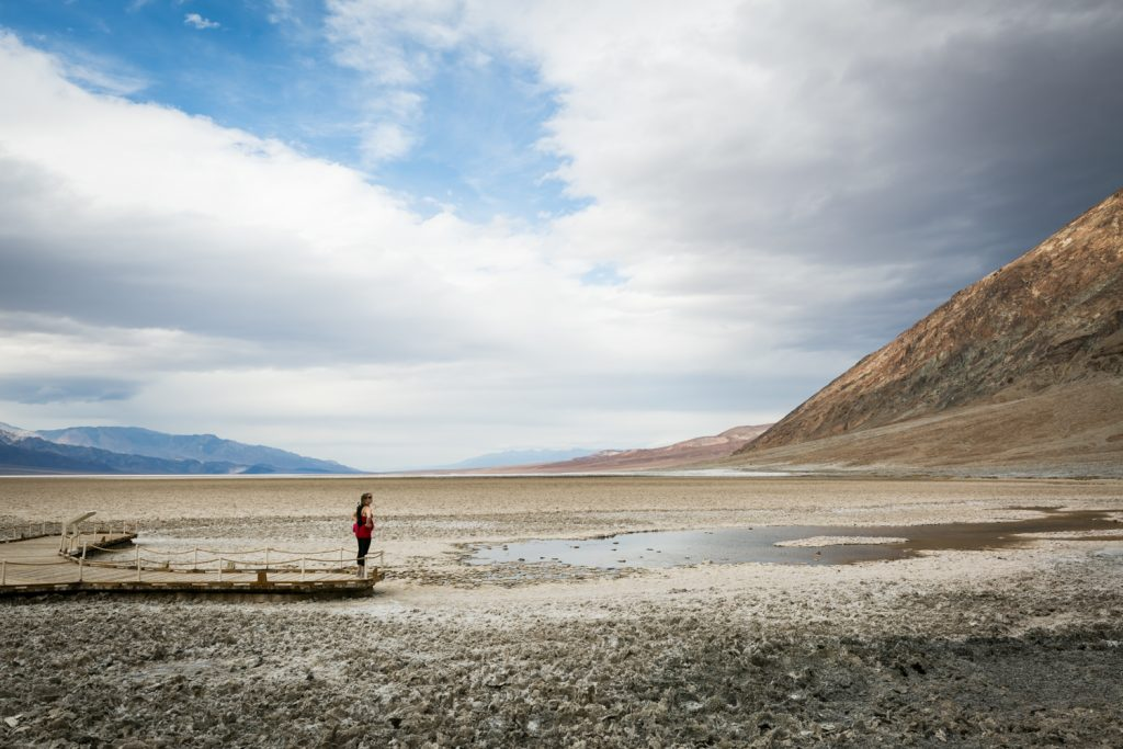 Female tourist looking at lake in Badwater in Death Valley National Park