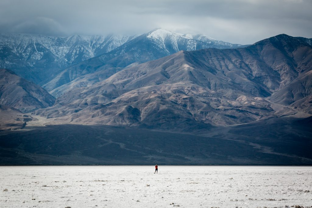 Lone tourist against mountains in Death Valley National Park