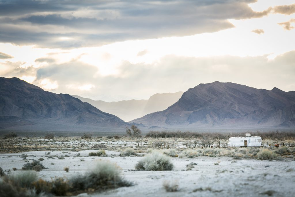 Light shining through clouds with mobile home in Death Valley National Park