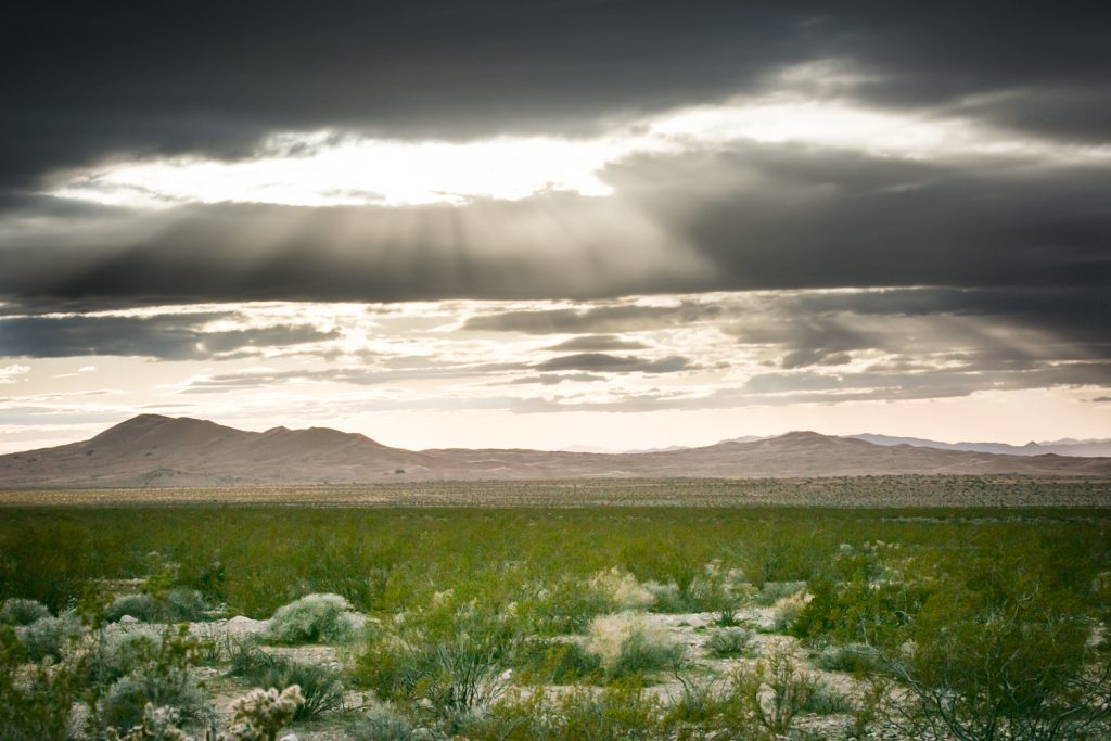 Light shining through clouds with mountains in Mojave National Preserve