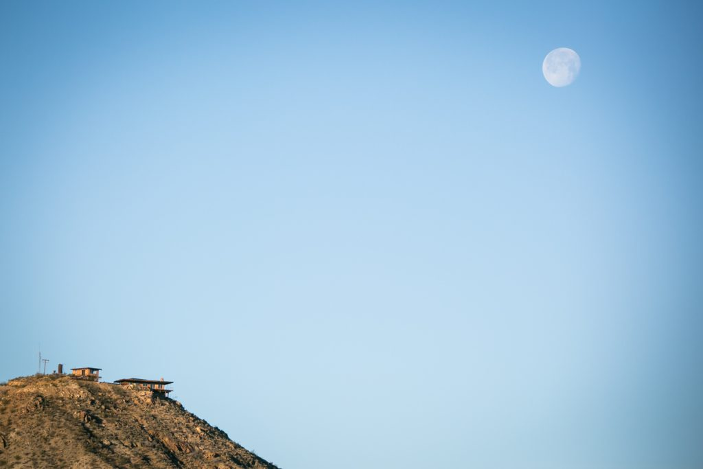 House on edge of mountain with full moon overhead during the day in Mojave National Preserve