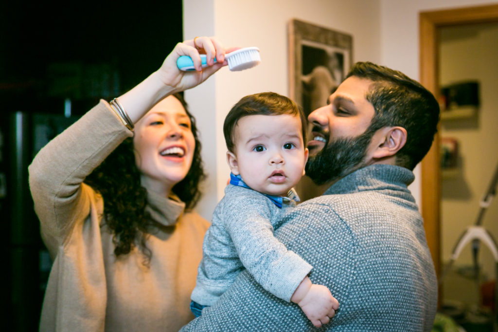 Parents brushing their child's hair for an article on indoor baby portrait tips