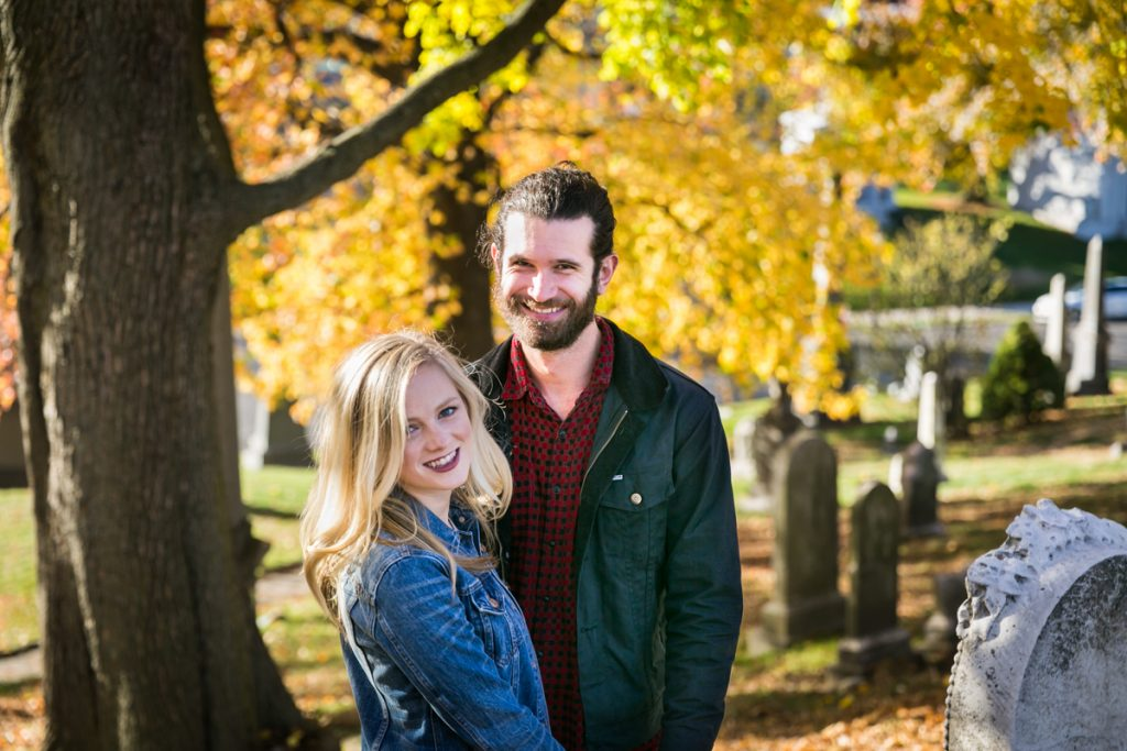 Green-Wood Cemetery engagement photos of couple under tree with yellow leaves
