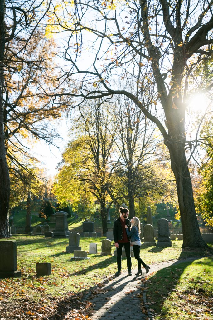 Green-Wood Cemetery engagement photos of couple walking between trees