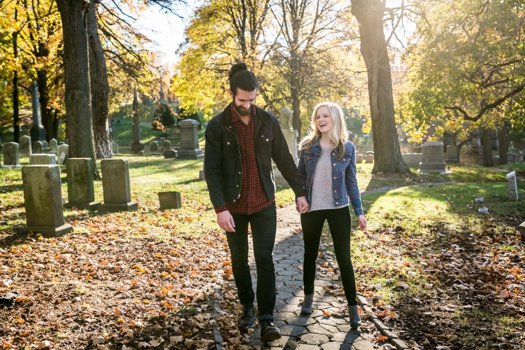 Green-Wood Cemetery engagement photos of couple holding hands and walking along path