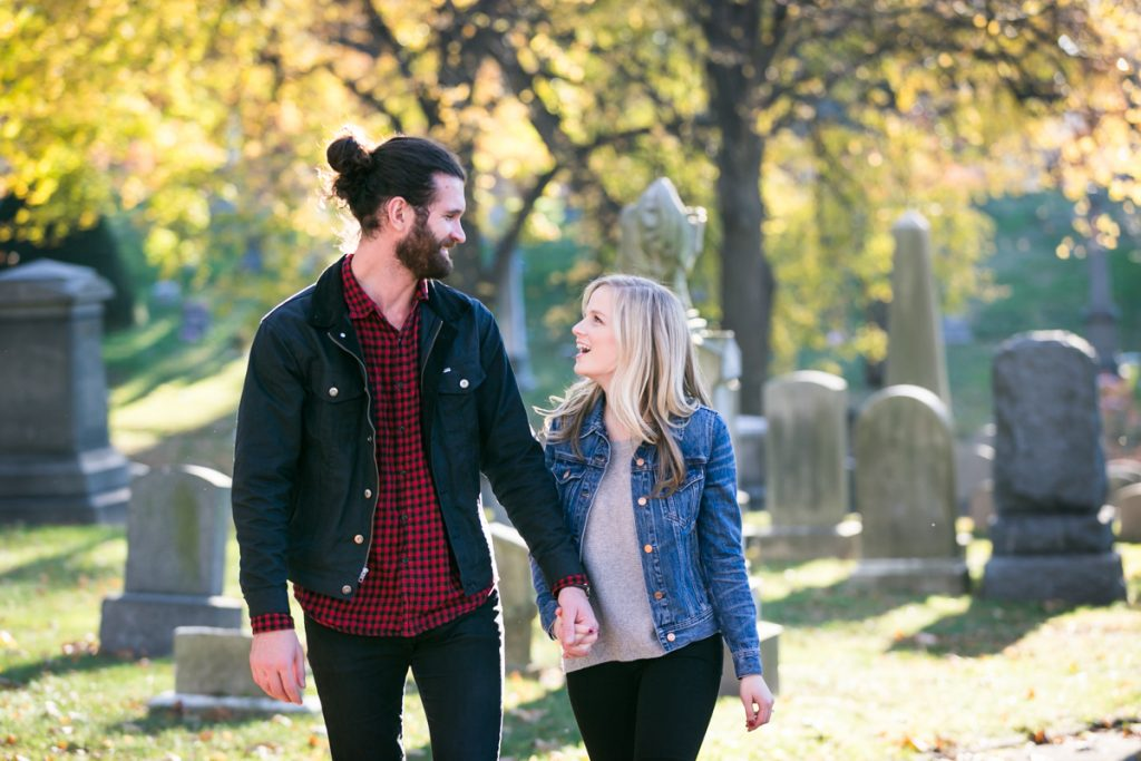 Green-Wood Cemetery engagement photos of couple walking in front of graves