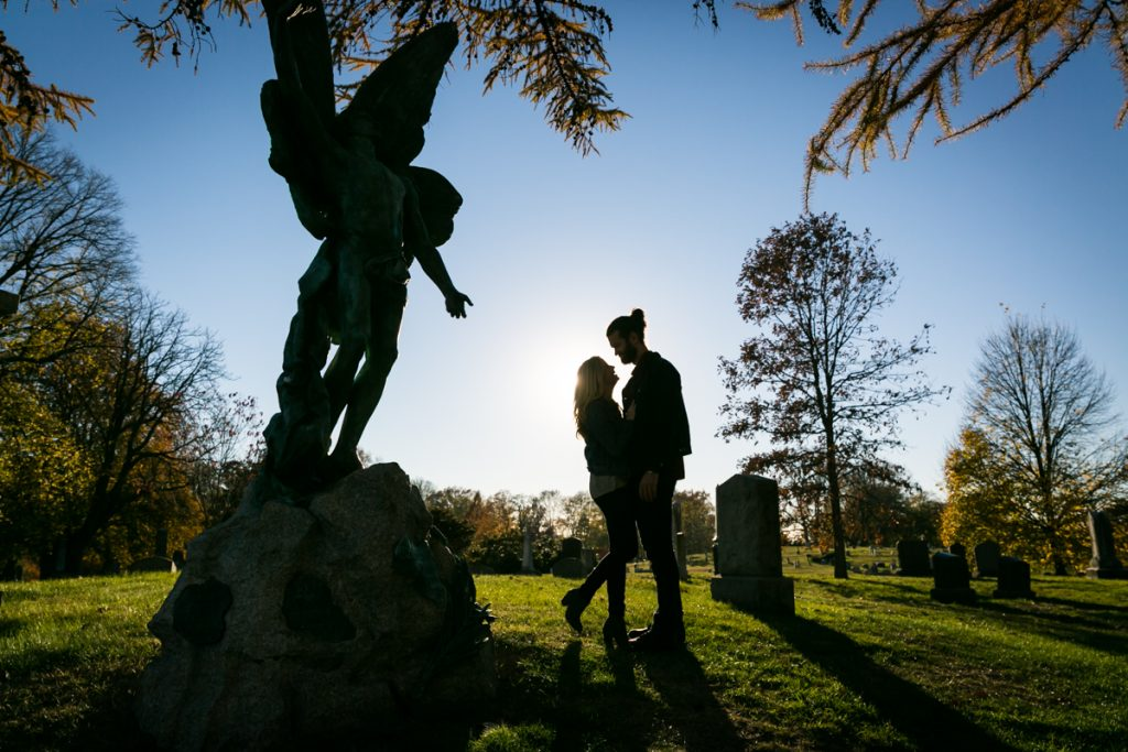 Green-Wood Cemetery engagement photos of backlit couple by angel statue