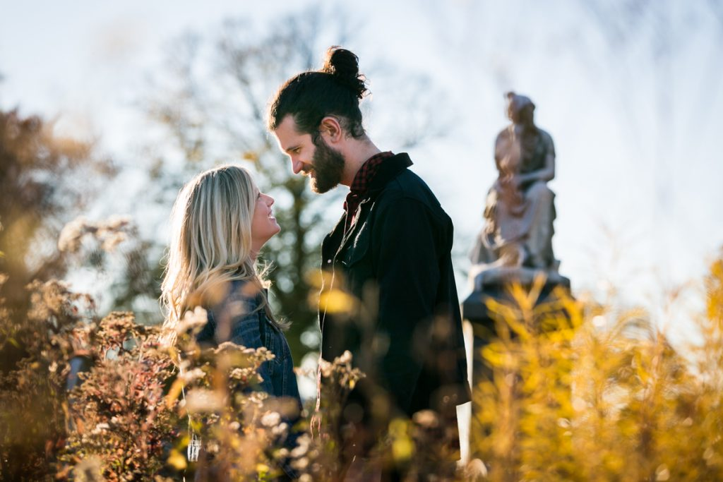 Green-Wood Cemetery engagement photos of couple behind bushes