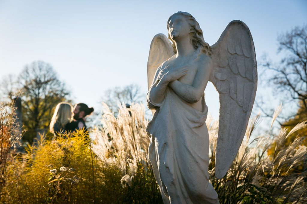 Green-Wood Cemetery engagement photos of couple hugging to side of angel statue